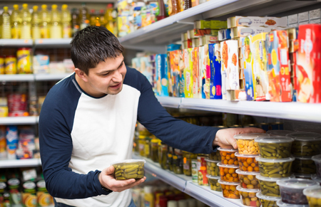 tinned: Positive young man buying tinned food at grocery store Stock Photo