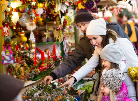 4s: Ordinary family with little girls standing at coniferous souvenirs counter. Focus on child in gray clothes Stock Photo