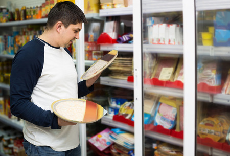 russian man: Happy russian man buying Italian pizza in cooled food section