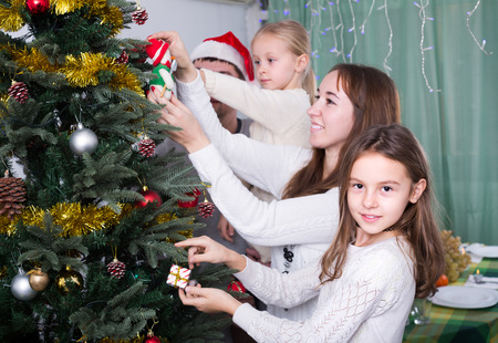 home decorating: Young parents with two children decorating Christmas tree at home. Focus on girl