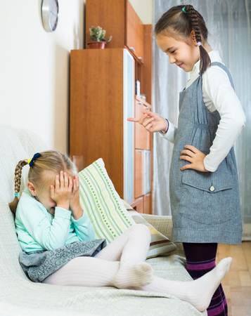 shaming: Annoying big sister preaching little one and shaking finger Stock Photo