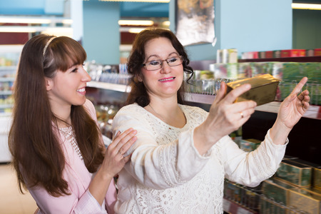 grocery shelves: Ordinary female buyers selecting tea on grocery shelves Stock Photo