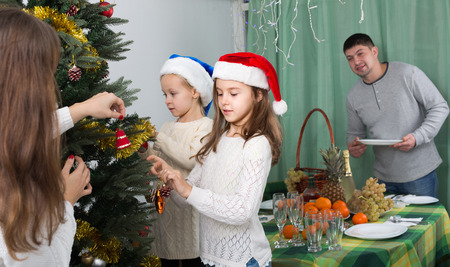 Two cute little girls and their young parents decorating Christmas tree at home. Focus on girl