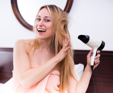 flyaway: Portrait of young smiling girl drying her hair with hairdryer in bedroom