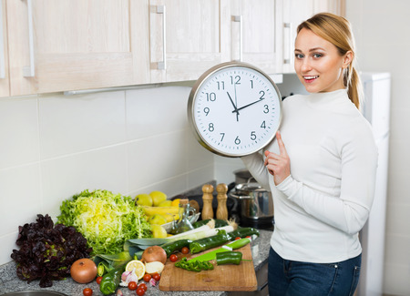 checking ingredients: Portrait of positive cheerful smiling woman holding clocks in domestic kitchen
