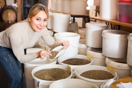 seeds of various: Cheerful smiling young woman picking various seeds for birds in shop
