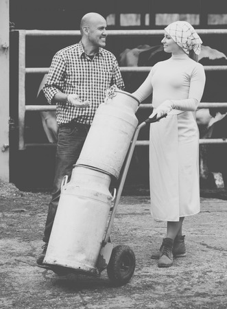 milk cans: Cheerful male and female farmers holding large metallic milk cans in hangar with cows