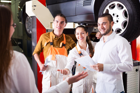 journeyman: Two troubleshooters and manager showing fixed car to cheerful client Stock Photo