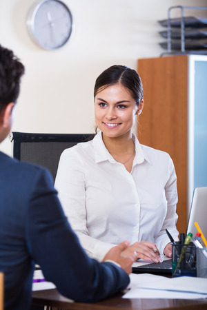conduction: Banking positive european agent listening to customer and smiling in agency