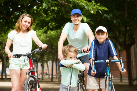 staying: Happy parents with children staying with bicycles in park
