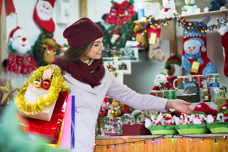 overspending: Beautiful happy smiling woman choosing Christmas decoration at market