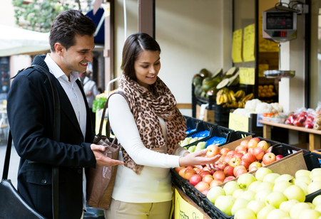 spouses: Young happy spouses choosing sweet fruits in grocery outdoors Stock Photo