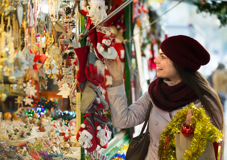 overspending: Cheerful smiling beautiful girl choosing Christmas decoration at market