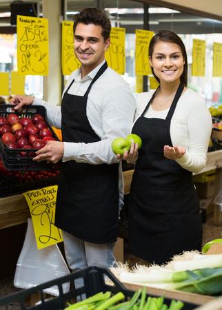 vendedores: vendedores sonriente ofreciendo manzanas dulces estacionales en la tienda de comestibles