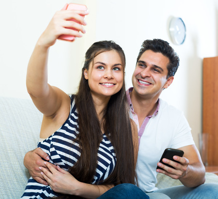 spouses: Happy young spouses posing and making selfie on smartphone. Focus on the woman Stock Photo