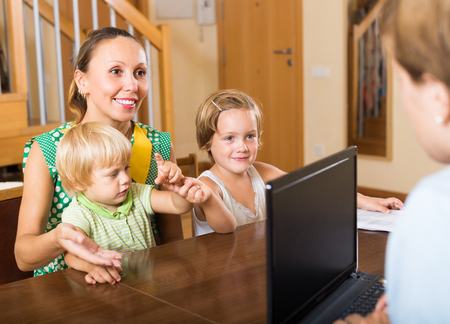 hypothec: Insurance agent consulting happy woman with two little children at home