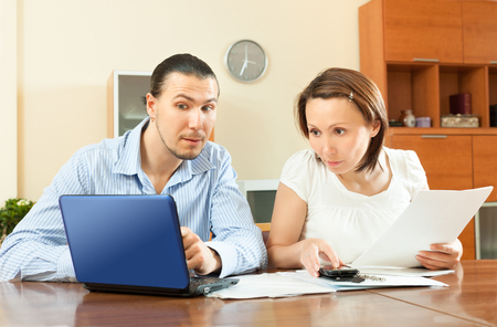 wistful: wistful couple calculating something at home Stock Photo