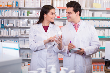 35 years: Smiling pharmacist 35 years old and pharmacy technician posing in drugstore Stock Photo