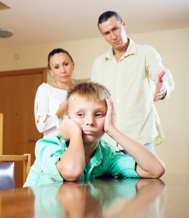 berate: Parents and teen son having quarrel at home. Focus on boy
