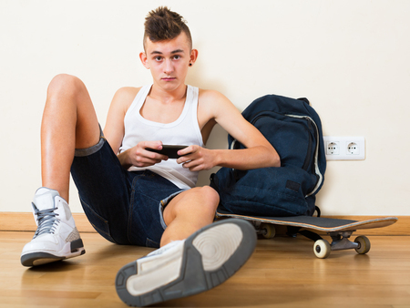 16s: Male teenager playing with a phone in the domestic interior Stock Photo
