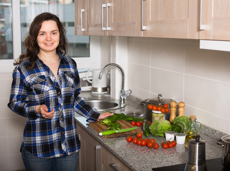 domestic kitchen: Cheerful housewife cooking vegetables at domestic kitchen