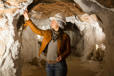 pit fall: Young female in leather jacket and helmet on salt-mine excursion at Cardona