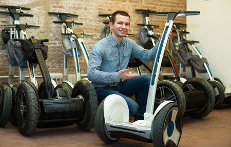 rental agency: Smiling male consultant in front of segways at rental agency