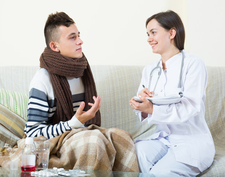 therapeutist: Male teenager with flue and professional therapeutist at home