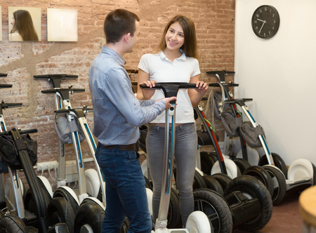 rental agency: Kindly female employee helping adult guy to select segway at rental agency