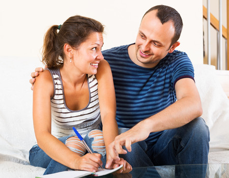 Happy spouses filling shopping list and smiling at home Imagens