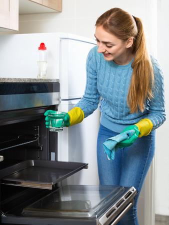 tabaco: La muchacha adulta positiva contenta alegre en quitarse los guantes tabaco en el horno Foto de archivo