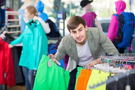 gladly: happy european man gladly choosing a sport shorts in the shop