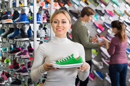 promoting: Smiling cheerful positive girl promoting shoes in the sport boutique Stock Photo