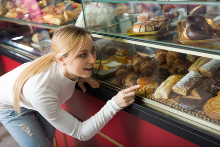 gladly: Young blond girl gladly choosing pastry in cafeteria store window