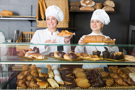 gladly: Cheerful woman and young girl gladly reccomending pastry in the cafe