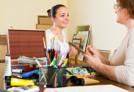 female likeness: Female artist painting portrait of smiling girl with pencil and paints in art studio Stock Photo