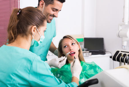 odontology: Young blonde female client and dental clinic crew during check up Stock Photo