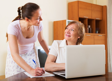calculated: Two smiling women looking financial documents in laptop at table in home interior