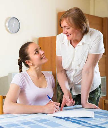 ruminate: Two smiling women signing financial documents at table in home interior