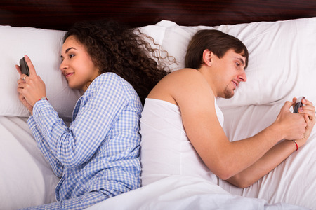 separately: Young married couple with mobile phones separately in bed Stock Photo