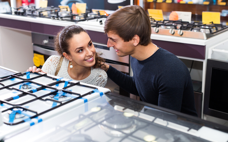 ordinary: Ordinary customers choosing gas hobs in hypermarket and smiling