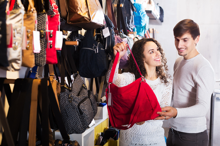 haberdashery: Young family couple purchasing leather bags in haberdashery shop