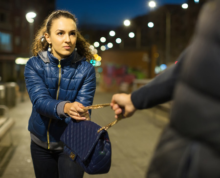to steal: Frightened young woman and robber trying to steal bag at night