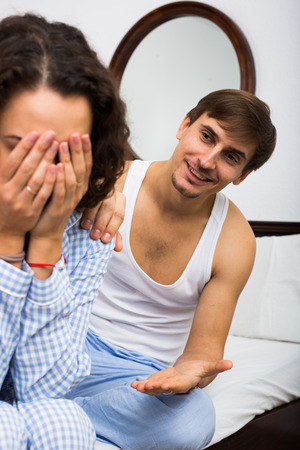 remit: Smiling man comforting offended wife in bedroom after quarrel