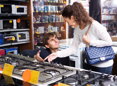 appliances: Young woman and man buying new gas-stove in appliances store Stock Photo