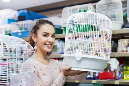 petshop: Portrait of smiling positive beautiful girl choosing bird cage in petshop Stock Photo
