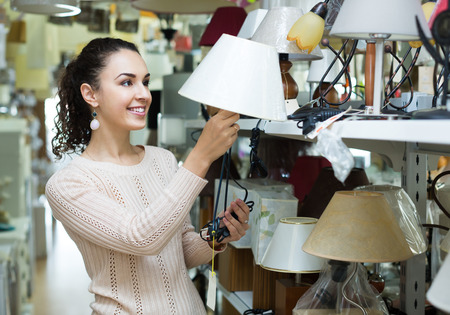 interior lighting: Woman buying lighting units for interior in household store
