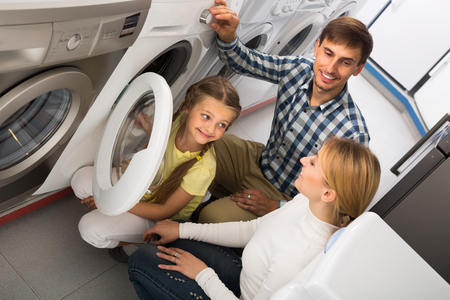 preparing food: Cheerful man and woman with girl buying washing machine in store with electronics