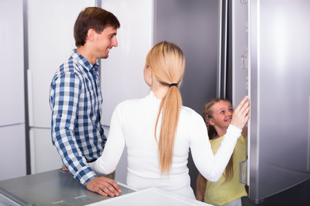 preparing food: portrait of  smiling customers selecting refrigerator in appliance store