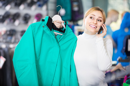 gladly: european girl gladly speaking on the phone and choosing a sport jacket